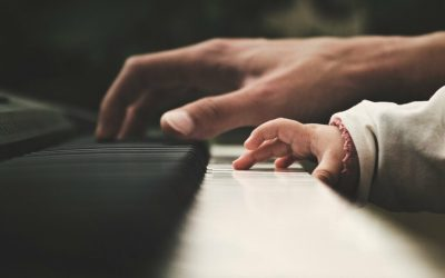 Adult and kid hands playing a keyboard