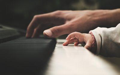 Imágen de las manos de un adulto y un niño tocando un piano